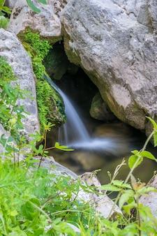 Pequeno rio pitoresco flui entre as pedras da floresta.