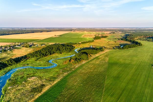 Pequeno rio que flui através de prados e campos agrícolas
