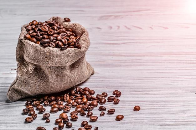 Pequeno saco de grãos de café e alguns grãos perto dele