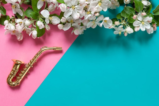 Pequeno saxofone dourado e galhos de macieira florescendo. vista superior, close-up em fundo de papel duotônico rosa pastel e azul claro