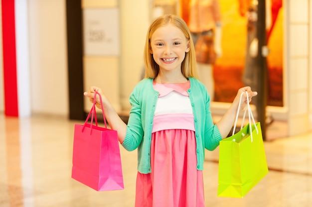 Pequeno shopaholic. menina alegre segurando uma sacola de compras colorida e sorrindo em pé no shopping