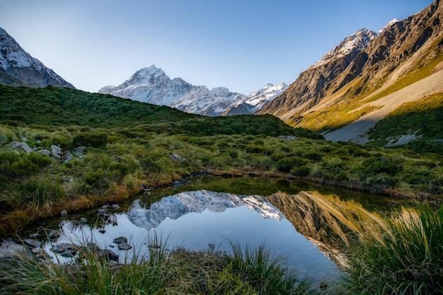 Pequeno tarn alpino no vale hooker, refletindo o monte cook de aoraki