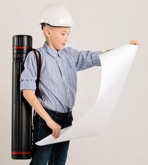 Pequeno trabalhador da construção civil segurando o projeto