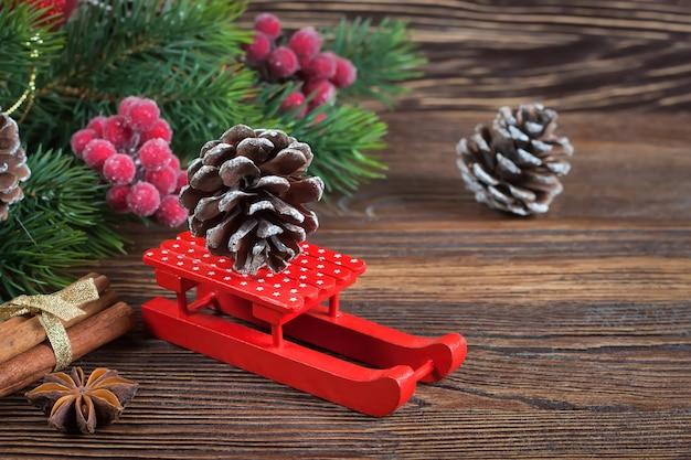 Pequeno trenó vermelho com cone de abeto e árvore de natal na mesa com fundo de madeira marrom