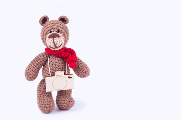 Pequeno urso de malha, feito à mão. amigurumi dia internacional da fotografia, concept