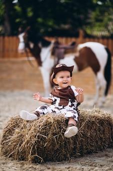 Pequeno vaqueiro sentado no feno