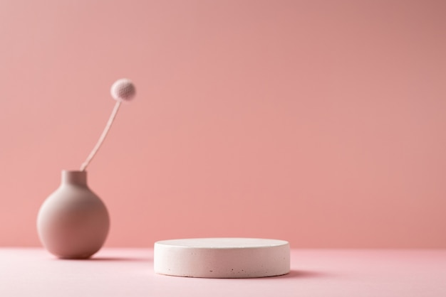 Pequeno vaso com flor seca e pódio de beton em um fundo rosa neutro nas sombras. fundo de composição minimalista, vista lateral do espaço de cópia