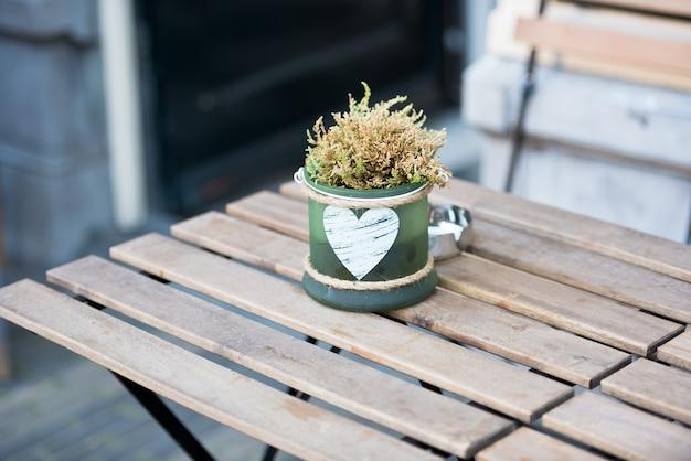 Pequeno vaso verde com flores e coração na mesa em um café ao ar livre