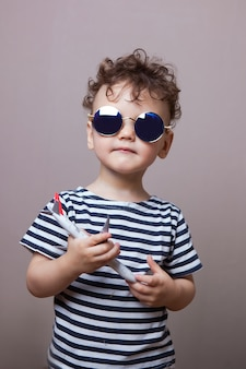 Pequeno viajante. criança feliz em um colete com um avião na mão