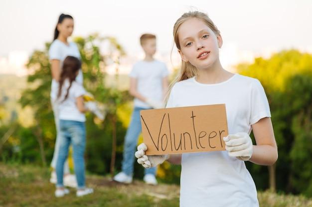 Pequeno voluntário ajudando a plantar árvores e arbustos em parques
