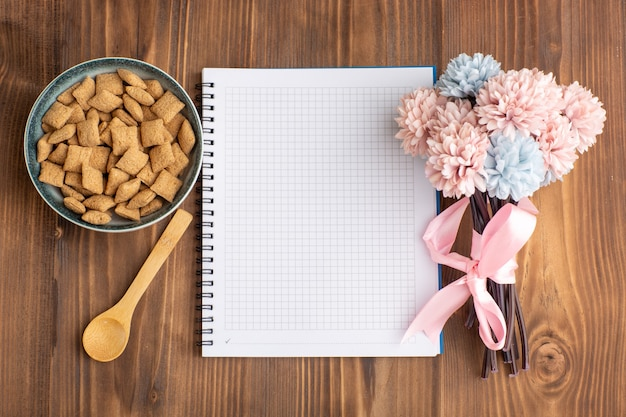 Pequenos biscoitos com bloco de notas na mesa marrom