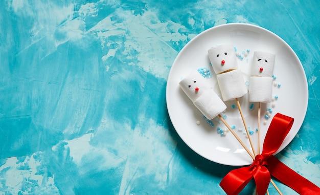 Pequenos bonecos de neve de marshmallows em varas. comida de natal.
