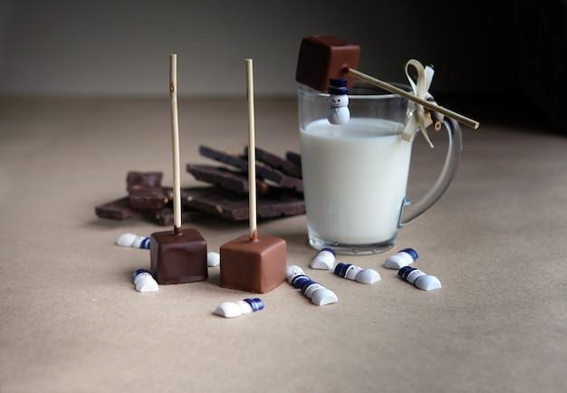 Pequenos bonecos de neve perto de cubos de chocolate em um palito com copo de leite e cacau aromático e chocolate em fundo marrom, close-up