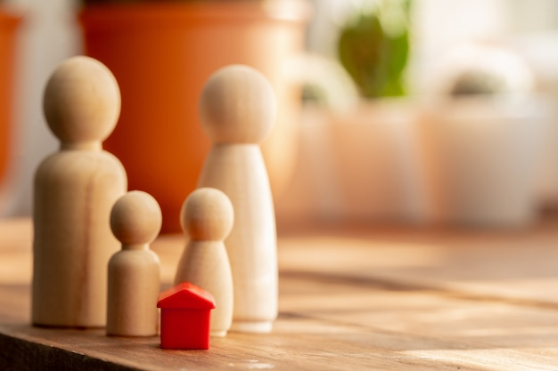 Pequenos brinquedos de madeira da família. compra de casa, venda, conceito de aluguel