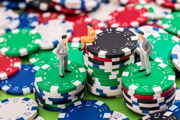 Pequenos brinquedos estão de pé e sentados em fichas de pôquer