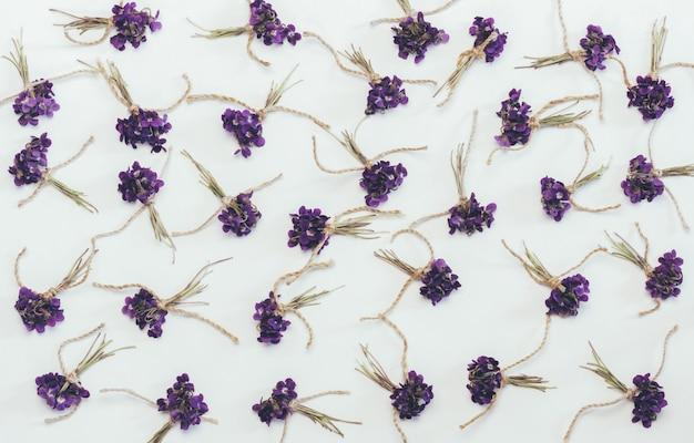 Pequenos buquês de flores perfumadas violetas flores brancas, vista superior plana leigos