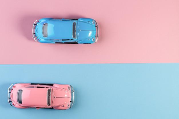 Pequenos carros de brinquedo retrô vintage em uma superfície rosa e azul