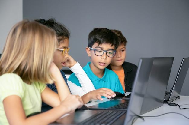 Pequenos colegas discutindo a lição e realizando tarefas