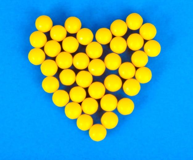 Pequenos comprimidos farmacêuticos médicos redondos amarelos, vitaminas, medicamentos, antibióticos na forma de um coração