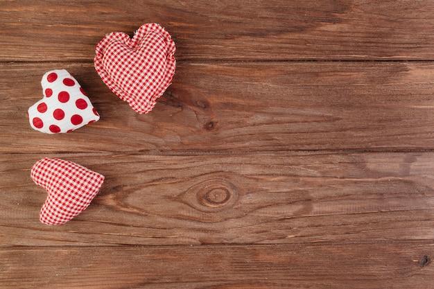 Pequenos corações brilhantes macias na mesa de madeira