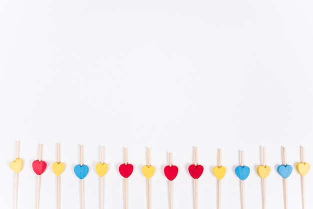 Pequenos corações de madeira em varas na mesa branca