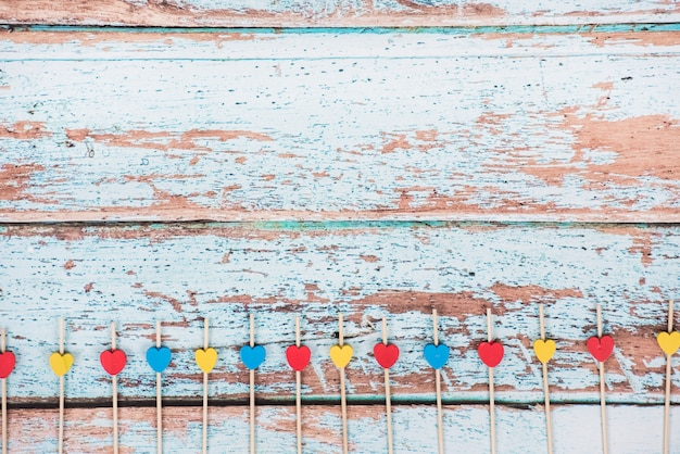 Pequenos corações de madeira em varas na mesa