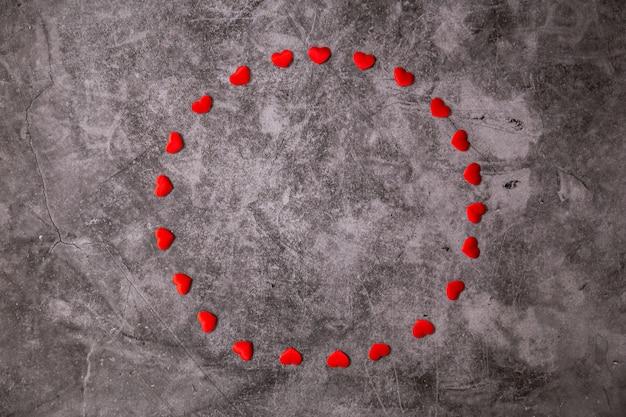 Pequenos corações vermelhos e brancos em uma pedra preta. molduras de dia dos namorados com copyspace