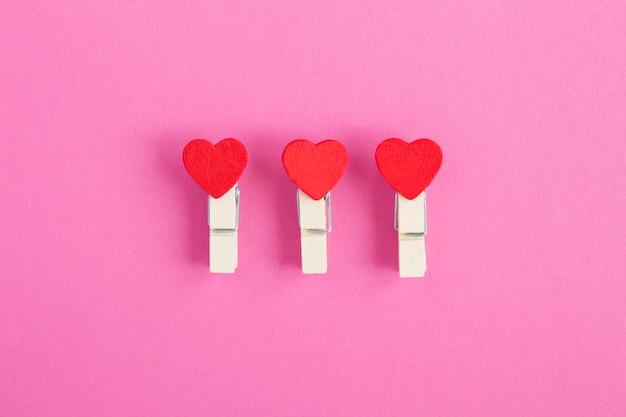 Pequenos corações vermelhos em prendedores de roupa de madeira