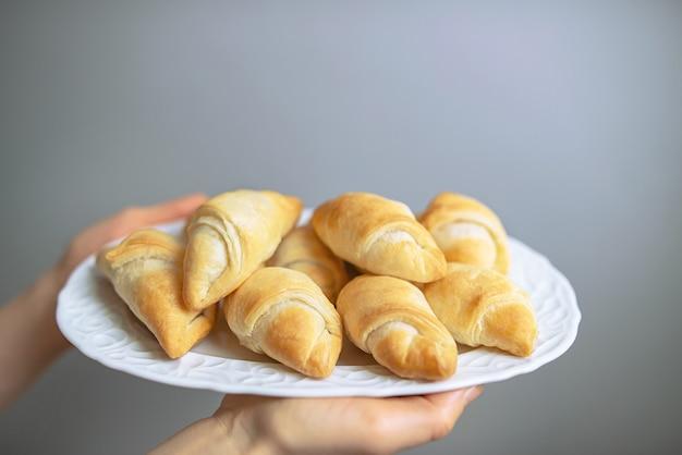 Pequenos croissants caseiros acabados de fazer num prato branco. mini croissants doces com geléia, espaço de cópia gratuita.