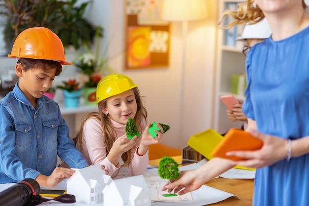 Pequenos engenheiros. futuros pequenos engenheiros se sentindo felizes enquanto estudavam modelagem de casas na escola primária