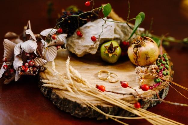 Pequenos frutos de romã, roseiras e espiguetas ao redor de alianças de ouro em uma prancha de madeira