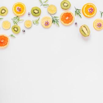 Pequenos galhos e flores perto de frutas sortidas