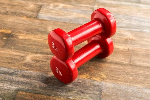 Pequenos halteres vermelhos no chão