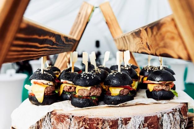 Pequenos hambúrgueres pretos em uma placa de madeira