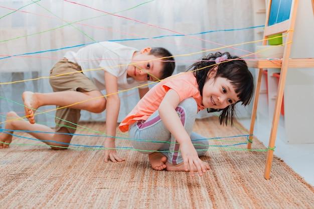 Pequenos irmãos brincando através de uma teia de corda