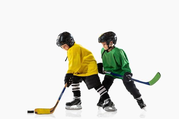 Pequenos jogadores de hóquei com os tacos na quadra de gelo e parede branca. desportistas com equipamento e treino de capacete. conceito de esporte, estilo de vida saudável, movimento, movimento, ação.