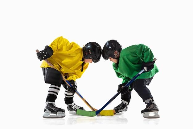 Pequenos jogadores de hóquei com tacos na quadra de gelo e parede branca do estúdio