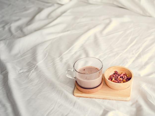 Pequenos lanches conjunto de feijões salgados e chocolate quente servido na cama.