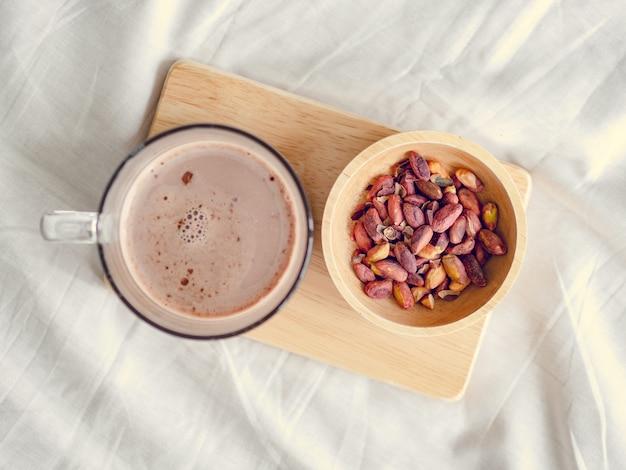 Pequenos lanches conjunto de feijões salgados e chocolate quente servido na cama