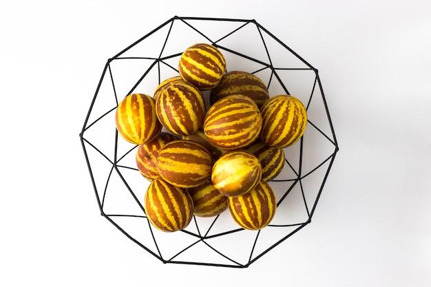 Pequenos melões vietnamitas em um vaso preto de hastes no estilo escandinavo. foco seletivo. vista do topo