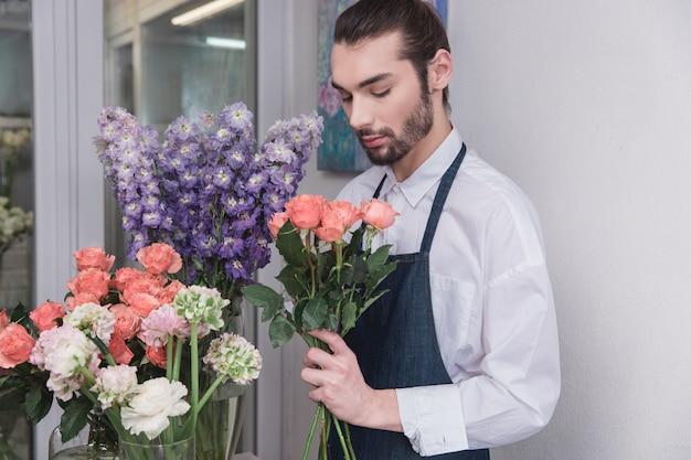 Pequenos negócios. florista masculina na loja de flores. fazendo decorações e arranjos Foto gratuita