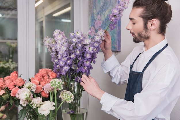Pequenos negócios. florista masculina na loja de flores. fazendo decorações e arranjos