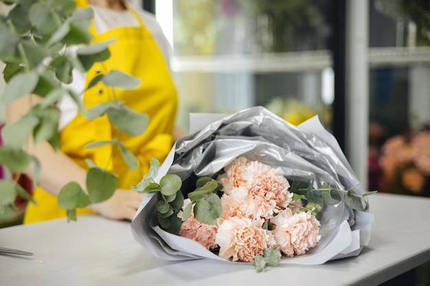 Pequenos negócios. florista sem foco na loja de flores. estúdio de design floral, fazendo buquê. entrega de flores, criando vista lateral do pedido