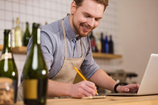 Pequenos negócios. homem alegre, positivo e simpático em pé no balcão e fazendo anotações enquanto trabalha em seu café