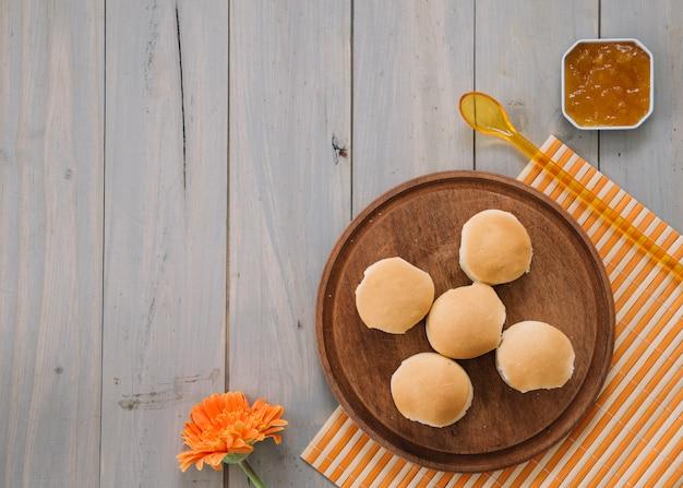 Pequenos pães na placa de madeira com geléia