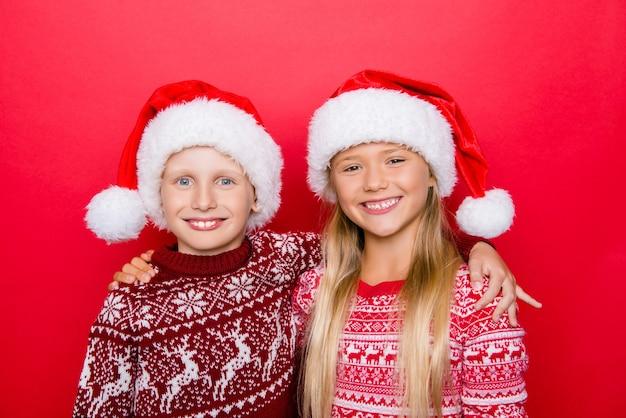 Pequenos parentes adoráveis e charmosos sorriem e se abraçam, se abraçando em roupas tradicionais de natal, posando isolados no espaço vermelho, animados, união e união. época sagrada do ano!