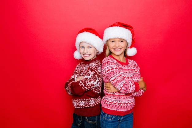 Pequenos parentes encantadores adoráveis sorriem, unindo-se em tradicionais roupas de malha x mas, jeans, posando isoladas no espaço vermelho, animado, união e união. época sagrada do ano!