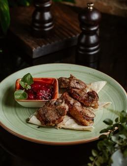 Pequenos pedaços de frango grelhados e servidos com molho de tomate e hortelã