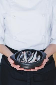 Pequenos peixes em uma tigela de cerâmica sobre as mãos do chef.