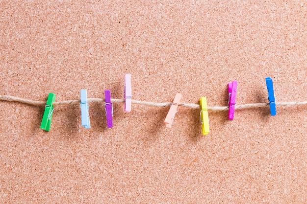 Pequenos prendedores de roupa de papel de madeira em uma corda contra um quadro de cortiça para anotações